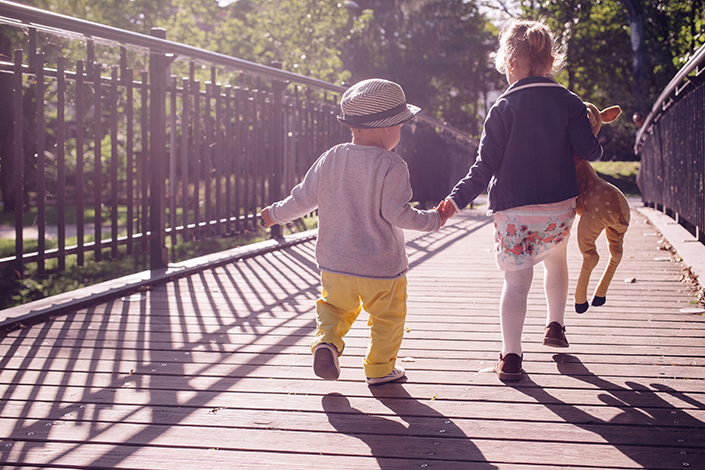 Two young children holding hands while walking across a bridge together.