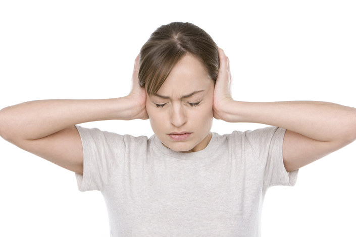 Frustrated, brunette Caucasian woman with her hands over her ears, eyes closed on white background.