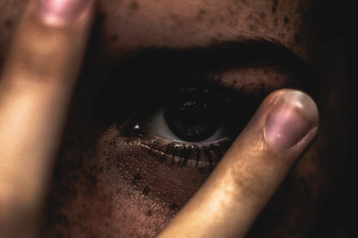 Close up of woman's eye with her fingers hovering over her eye and brows