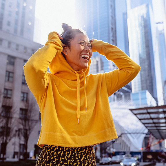 Woman in bright yellow hoodie smiling