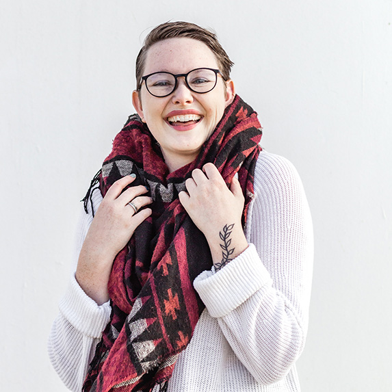 Person in shawl with glasses with a big smil
