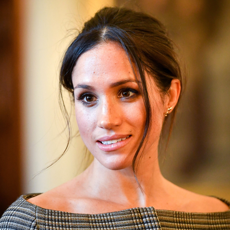 A closeup of Meghan Markle with her hair pulled back, looking off camera with a small smile on her face