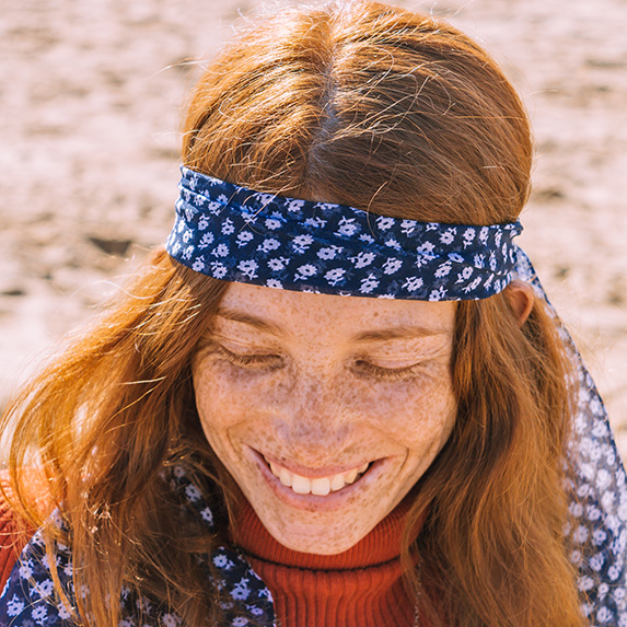 Woman with freckles and a headband looking down and smiling