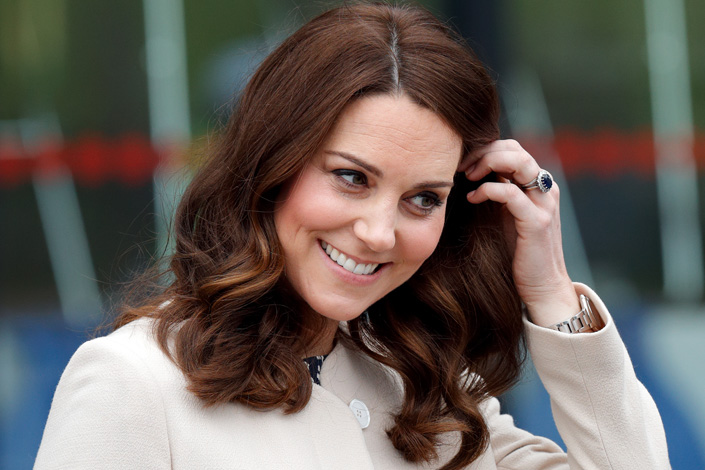Kate Middleton pushes back a lock of hair, revealing the large blue engagement ring she inherited from Princess Diana