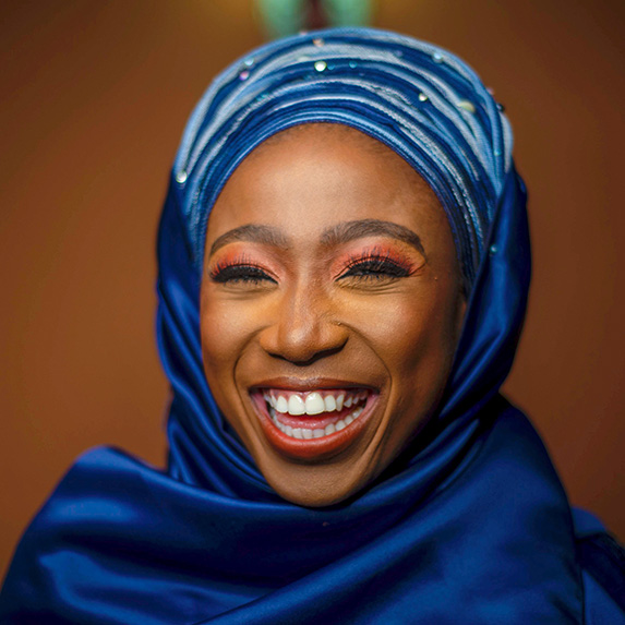 Woman in blue hijab grinning brightly