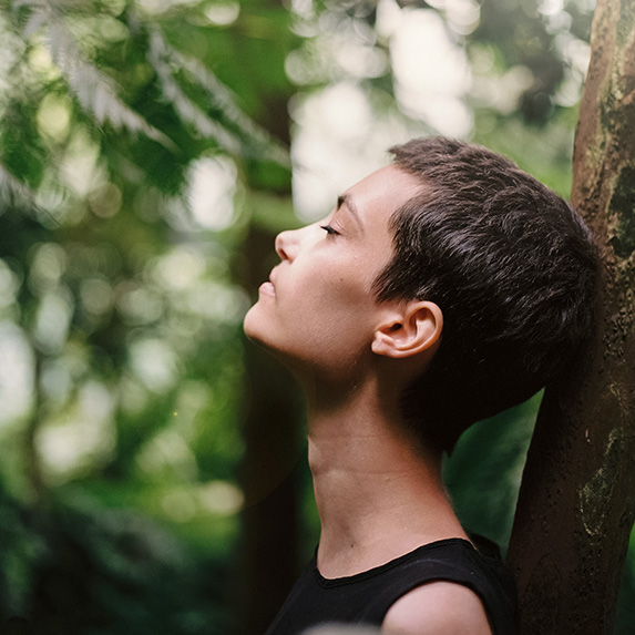 Woman leaning head against the tree, taking a mindful breath